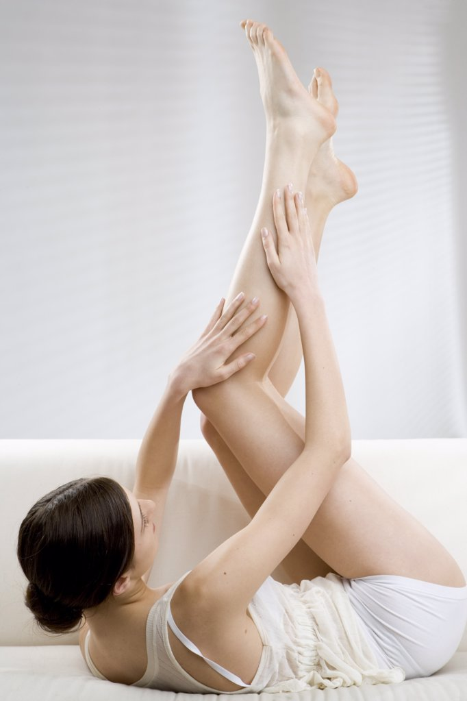 Stock Photo: 1841R-104069 young woman with legs up