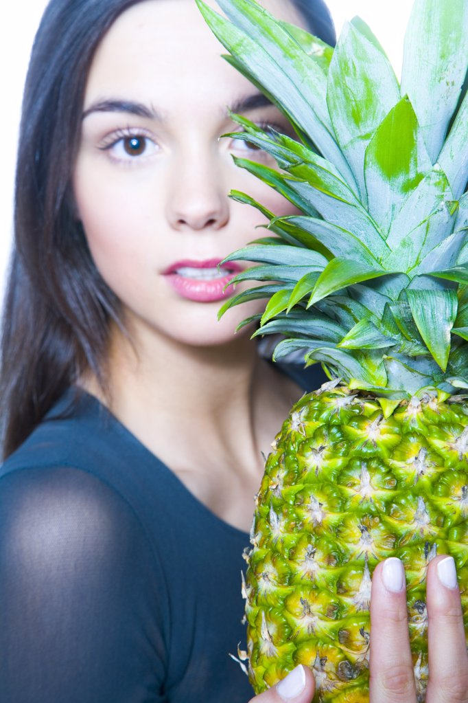 Stock Photo: 1841R-104252 young woman holding pineapple