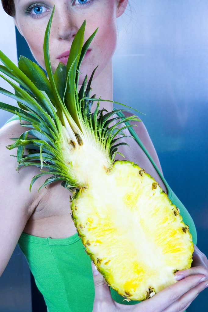 Stock Photo: 1841R-104260 young woman holding pineapple