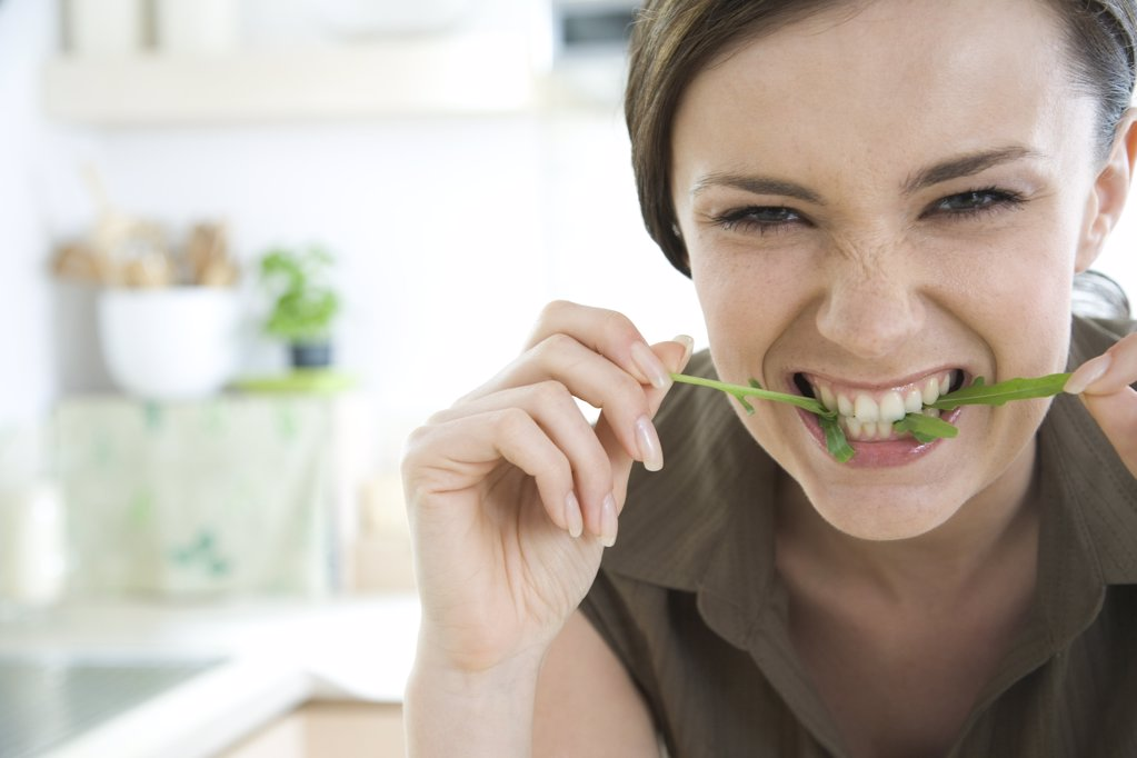 Stock Photo: 1841R-104669 woman biting rocket leaf