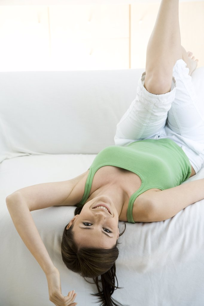 smiling woman lying on sofa : Stock Photo