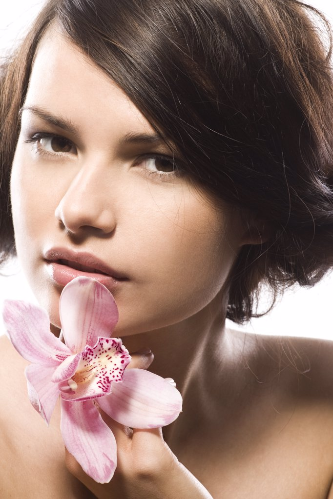 Stock Photo: 1841R-107141 young woman with pink orchid
