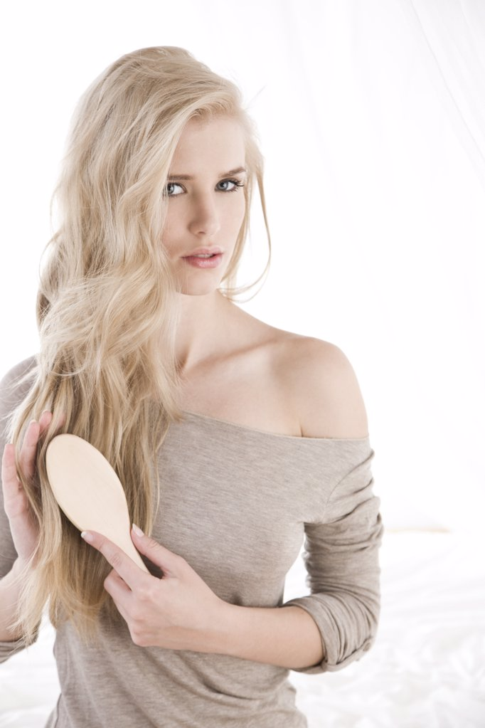 Young woman combing hair : Stock Photo