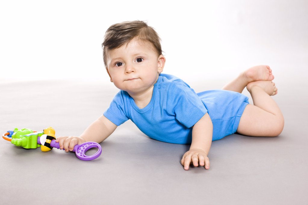 Baby on floor with toy : Stock Photo