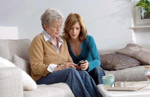 Stock Photo: 1841R-108295 Mother and daughter sitting on sofa