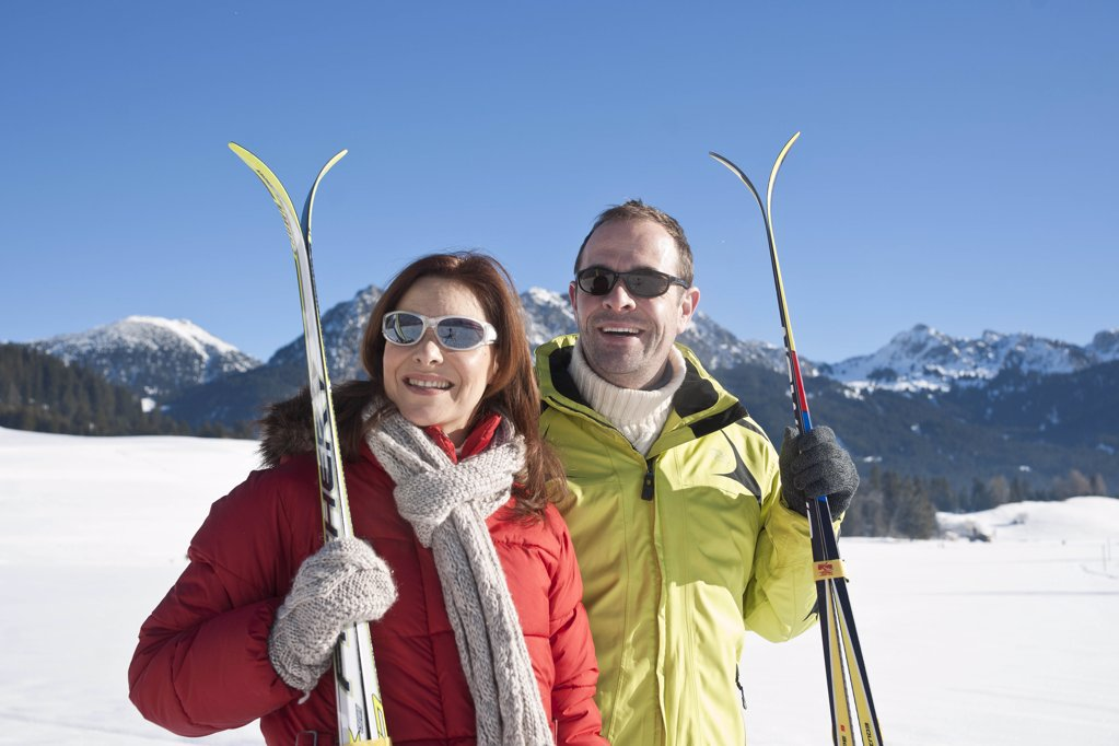 Stock Photo: 1841R-108463 Smiling couple with skis in winter landscape, Tannheimer Tal, Tyrol, Austria