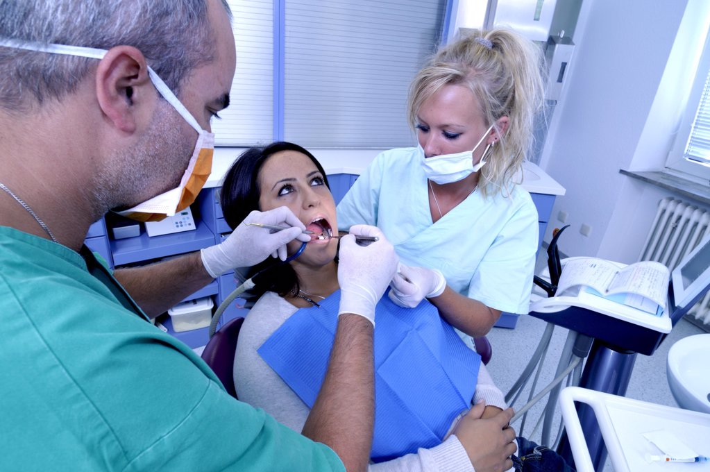 Stock Photo: 1841R-111432 female patient at the dentist sitting at the surgery couch  - dentist's assistant in the back