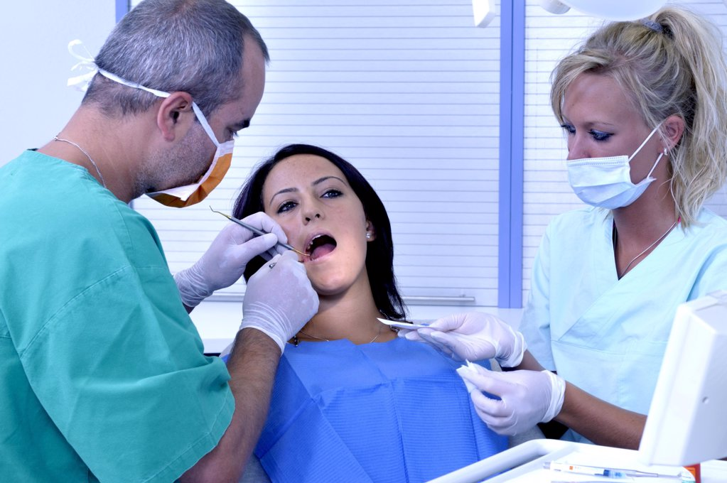 Stock Photo: 1841R-111434 female patient at the dentist sitting at the surgery couch  - dentist's assistant in the back