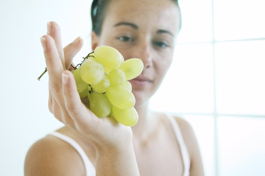 Young woman holds a bunch of grapes.. : Stock Photo