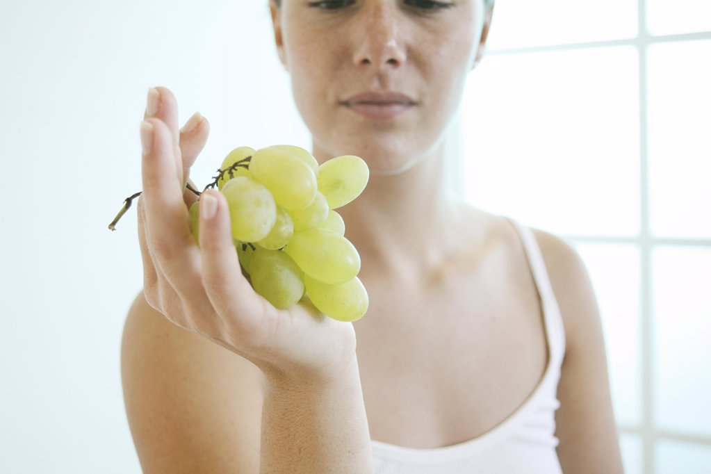Stock Photo: 1841R-111571 Young woman holds a bunch of grapes..