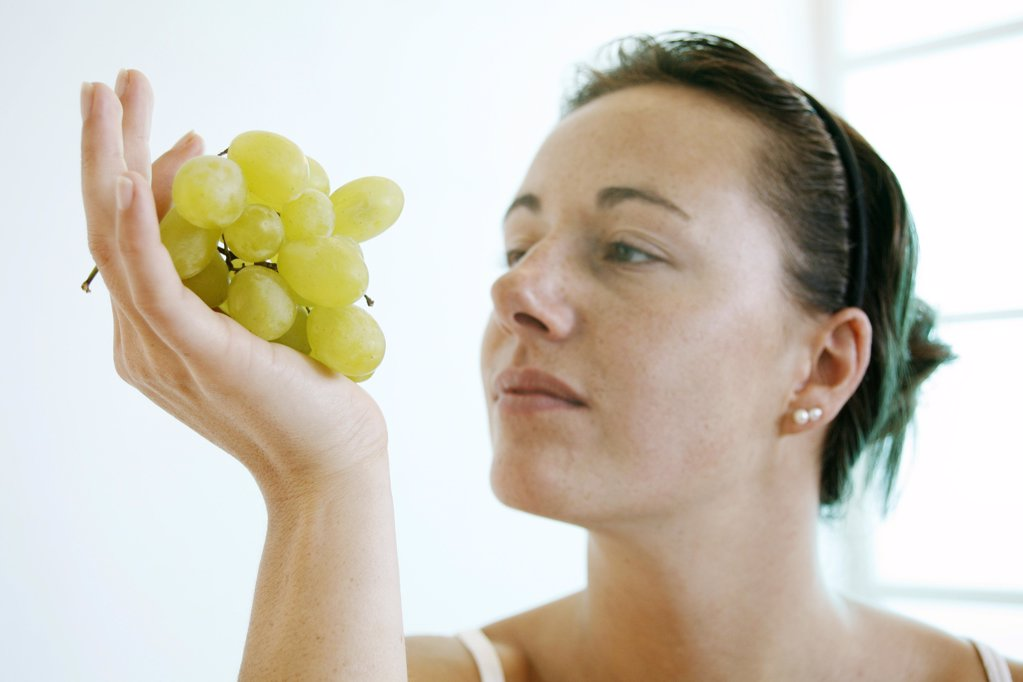Stock Photo: 1841R-111572 Young woman is looking at a bunch of grapes.