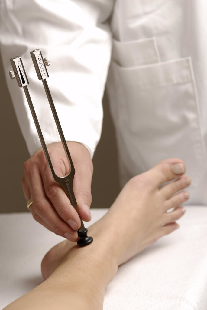 Stock Photo: 1841R-111636 Neurology : Examination of perception of vibration with  tuning fork . On , für example , polyneuropathy this is restricted