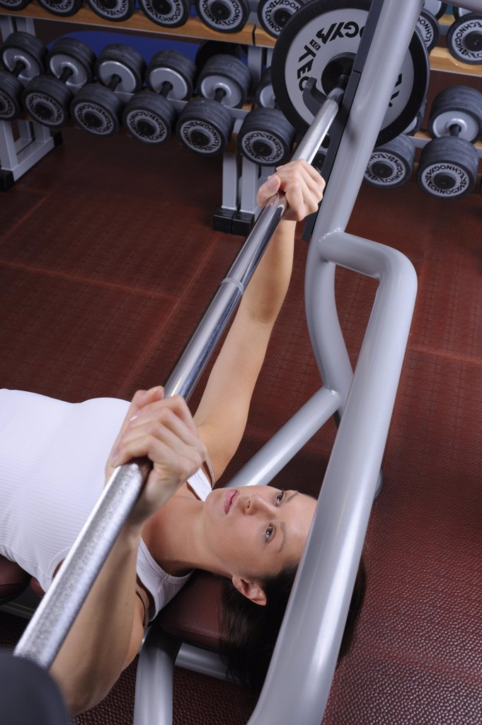 Stock Photo: 1841R-112075 young woman in a fitness center weight lifting