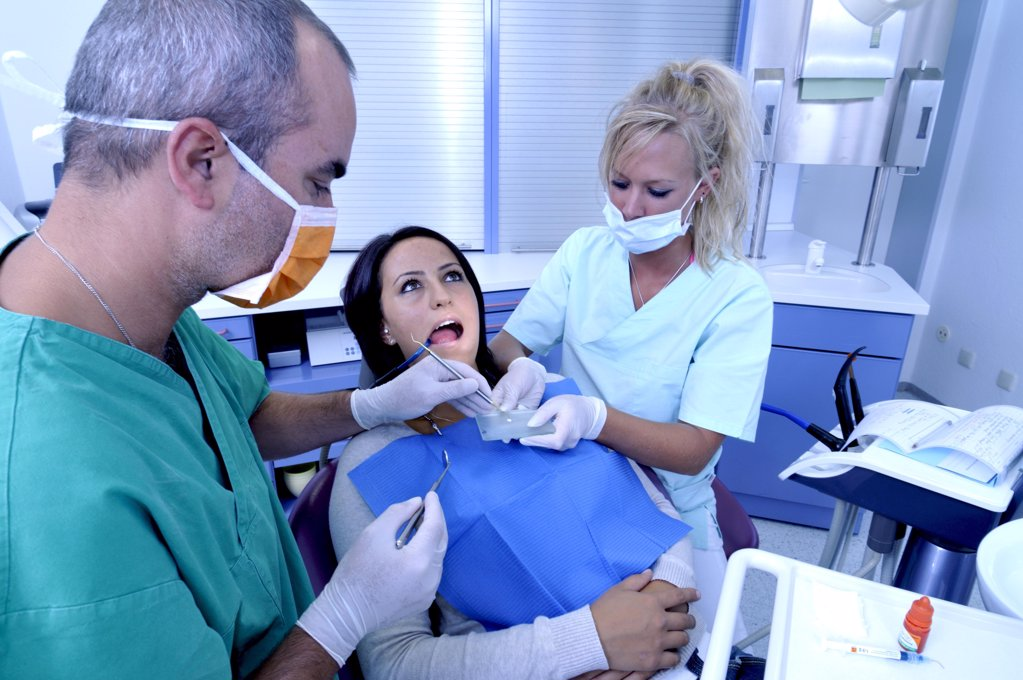 Stock Photo: 1841R-113076 female patient at the dentist sitting at the surgery couch  - dentist's assistant in the back