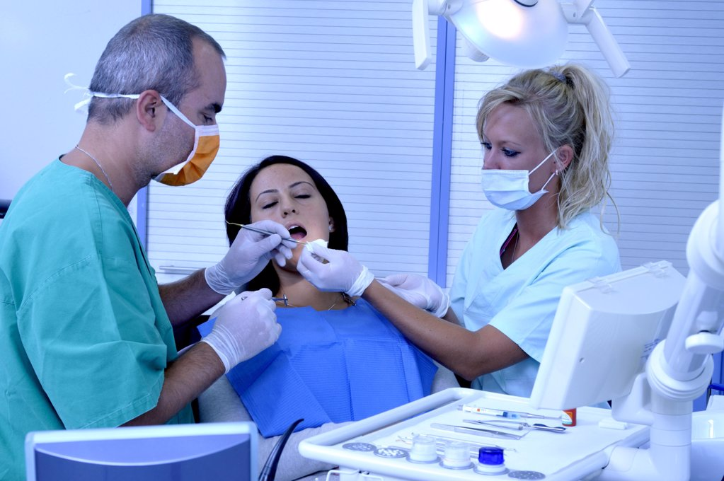 female patient at the dentist sitting at the surgery couch  - dentist's assistant in the back : Stock Photo