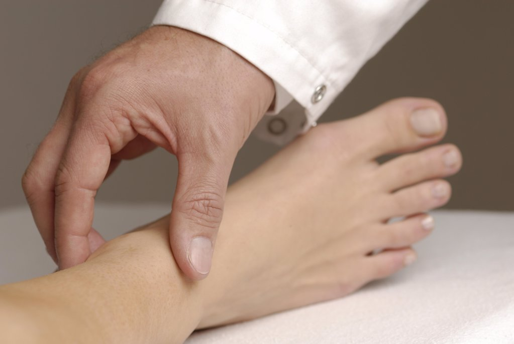 Physical examination : Palpation of pulse of Arteria tibialis posterior : Stock Photo