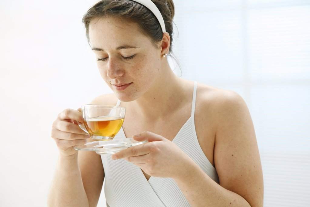 young woman holding a cup of tea in her hands and is taking a smell on it : Stock Photo