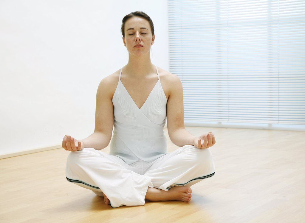 Stock Photo: 1841R-113358 young woman sitting on the floor and is meditating