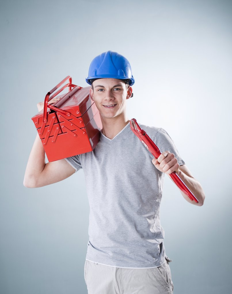 Stock Photo: 1841R-113984 Young man wearing hard hat holding tools, portrait