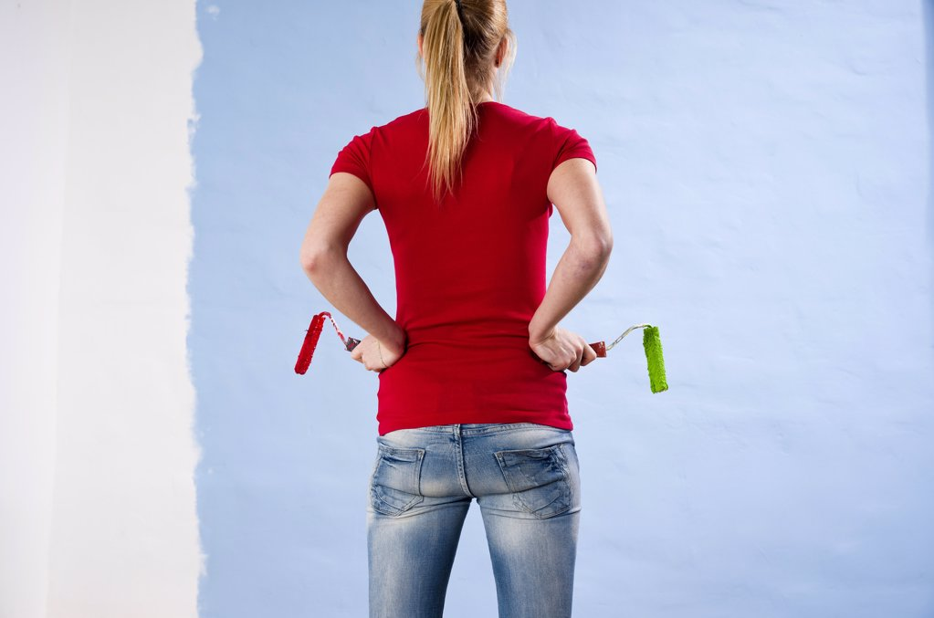 Stock Photo: 1841R-114036 Young woman painting a wall