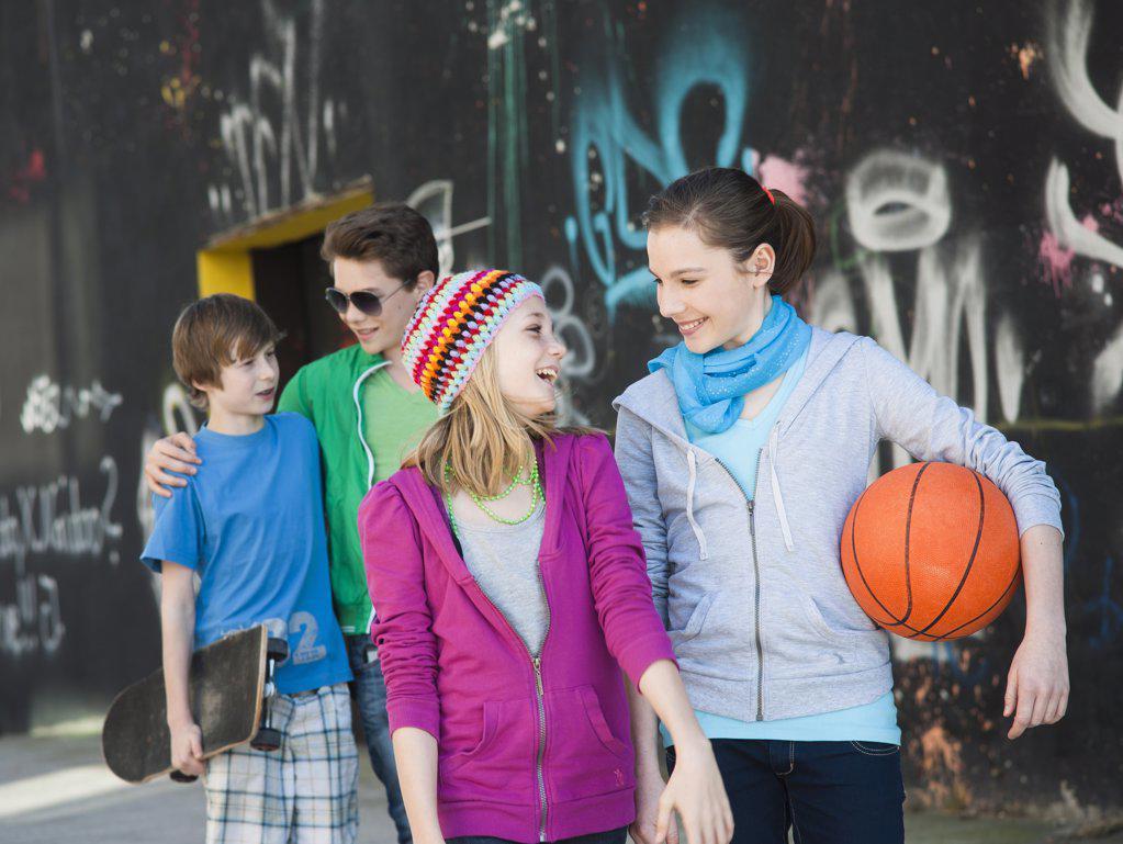 Four happy teenage friends walking at graffiti wall : Stock Photo