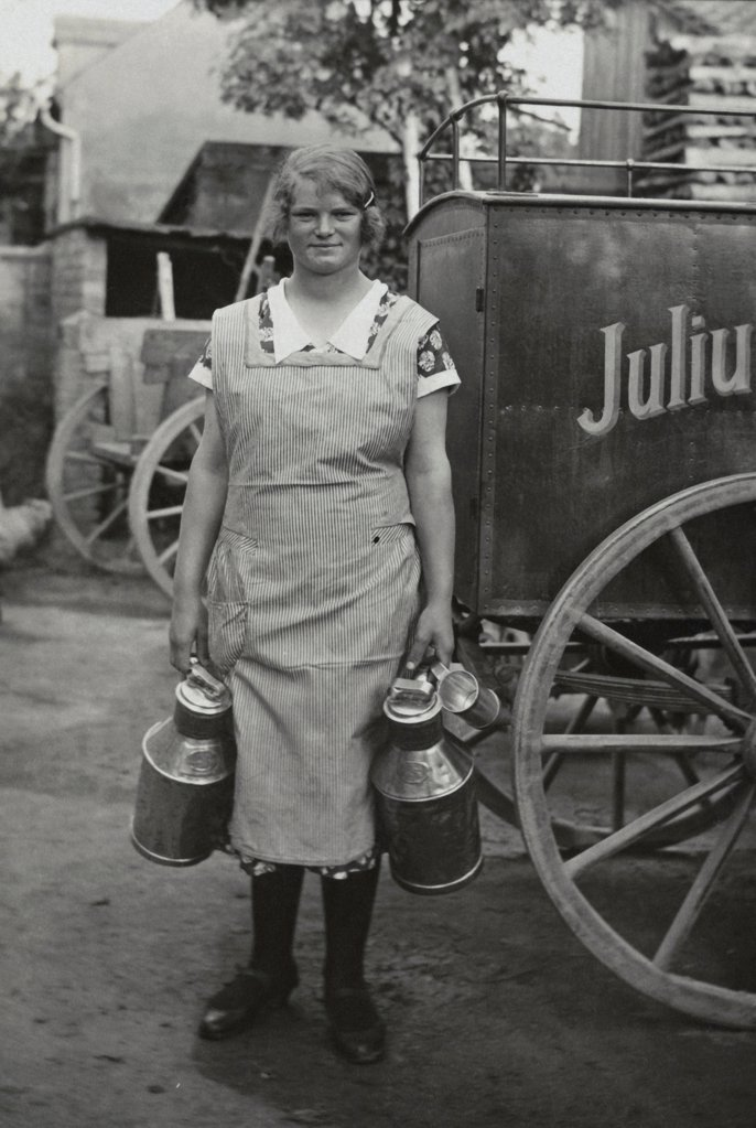 Historical picture of a farmers wife with milk cans : Stock Photo
