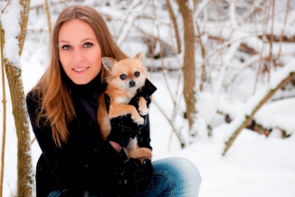 Stock Photo: 1841R-124839 Young woman with dog in snow, portrait