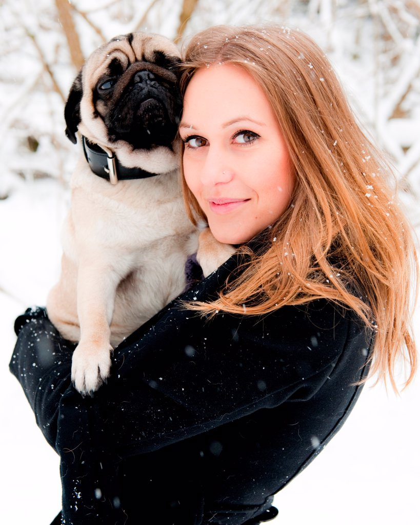 Young woman with pug dog in snow, portrait : Stock Photo
