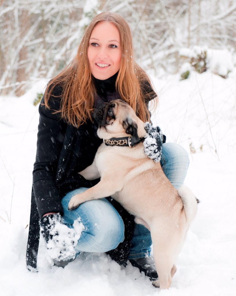 Young woman with pug dog in snow : Stock Photo