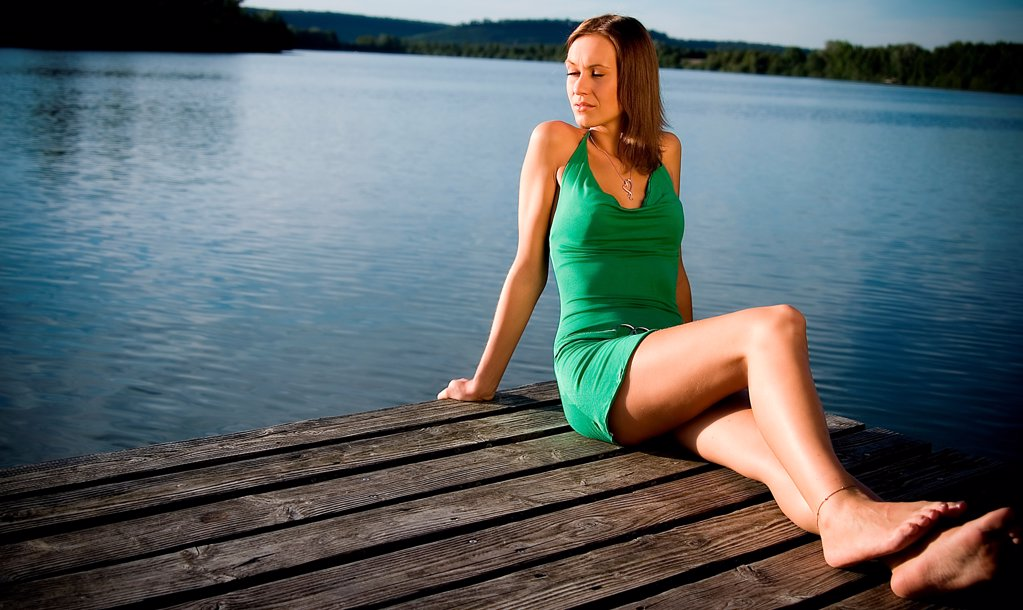Young woman in green dress at a lake : Stock Photo
