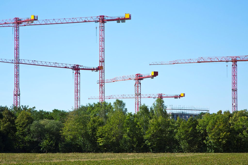 Stock Photo: 1841R-124891 Cranes on a construction site near a field
