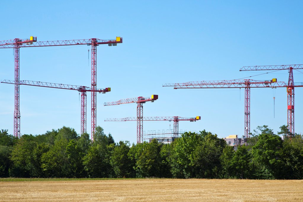 Stock Photo: 1841R-124892 Cranes on a construction site near a field