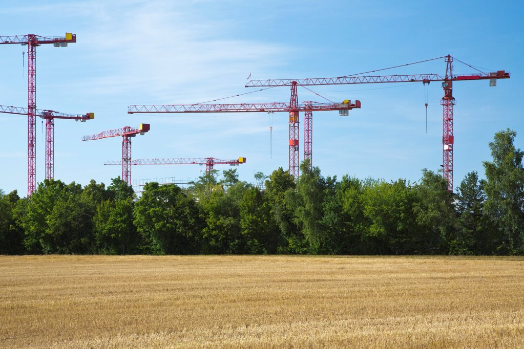 Stock Photo: 1841R-124896 Cranes on a construction site near a field