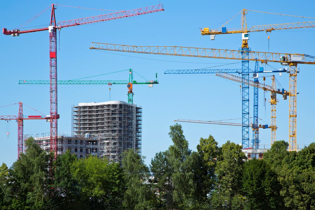 Stock Photo: 1841R-124901 Cranes on a construction site near a field