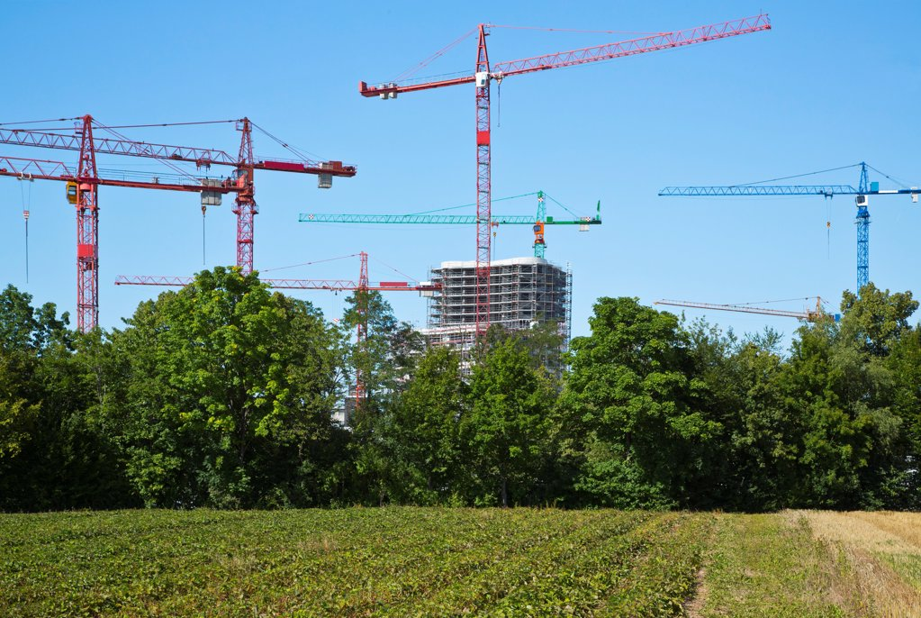 Cranes on a construction site near a field : Stock Photo
