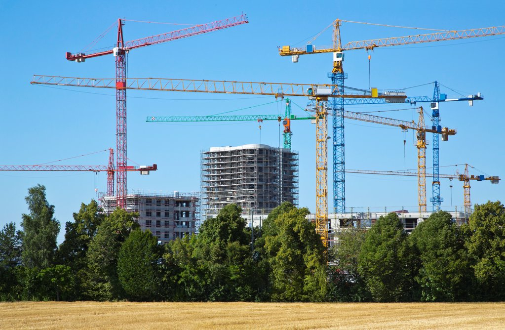 Stock Photo: 1841R-124907 Cranes on a construction site near a field