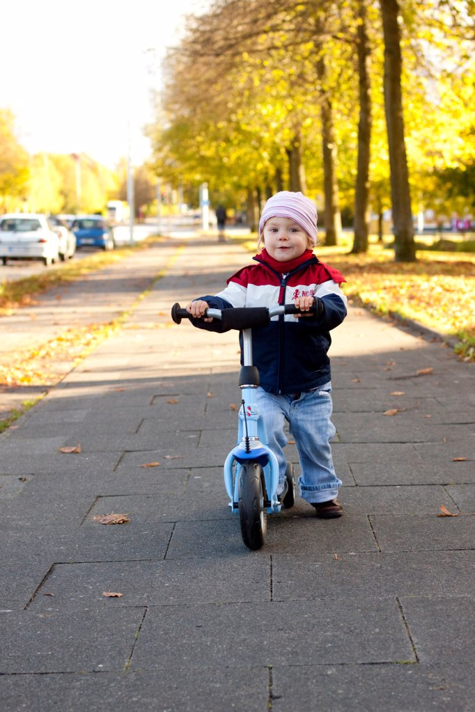 Stock Photo: 1841R-124925 Toddler with scooter on sidewalk