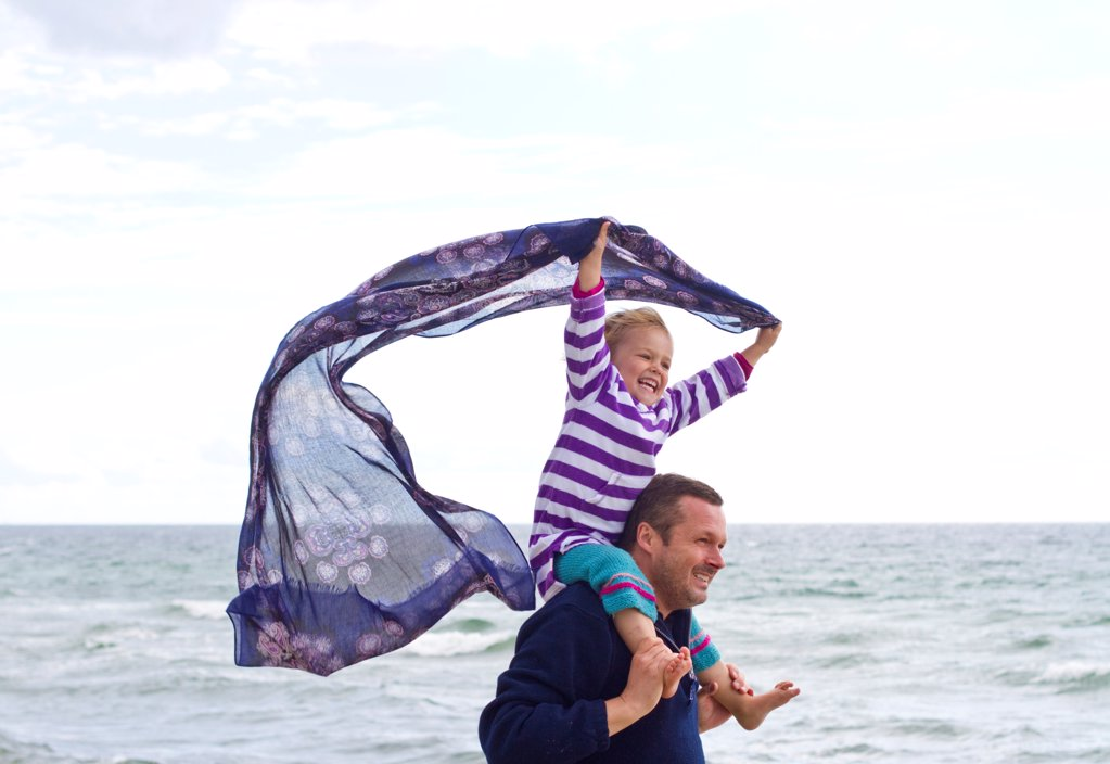 Father carrying daughter on shoulders on the beach : Stock Photo