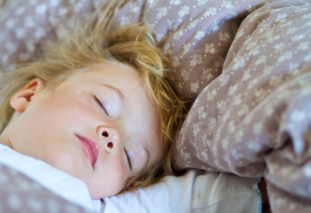 Blond girl sleeping in bed : Stock Photo