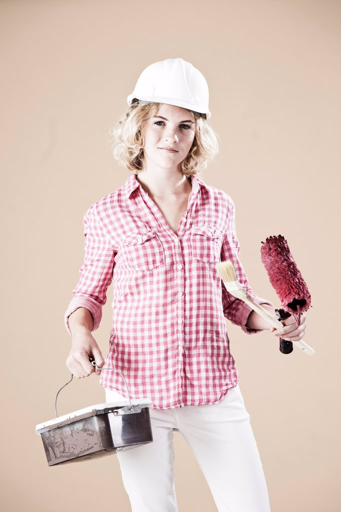 Teenage girl with hard helm and paint bucket : Stock Photo