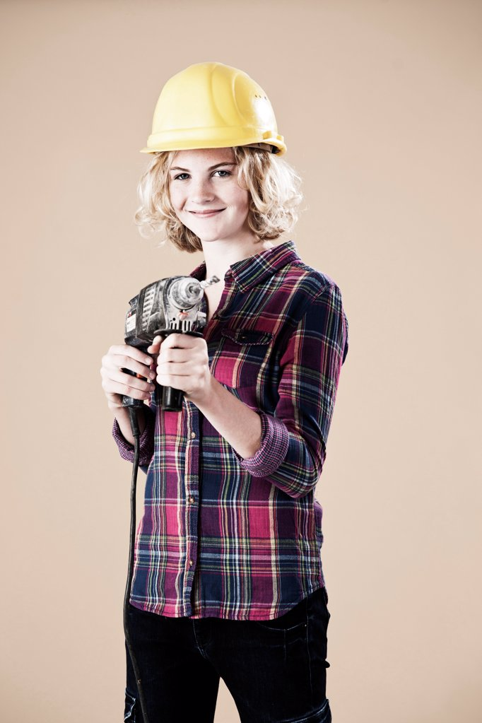 Teenage girl with hard helm and drill machine : Stock Photo