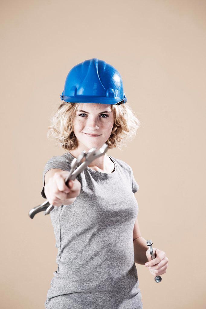Teenage girl with hard helm and hand tool : Stock Photo