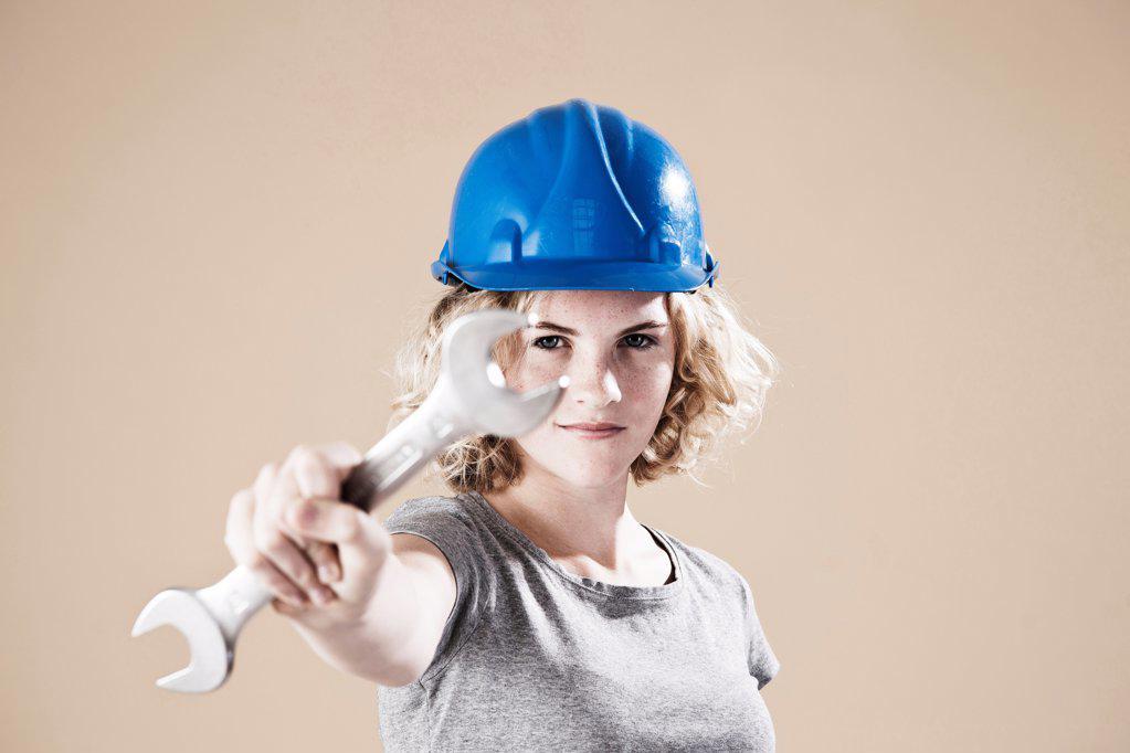 Stock Photo: 1841R-124963 Teenage girl with hard helm and hand tool