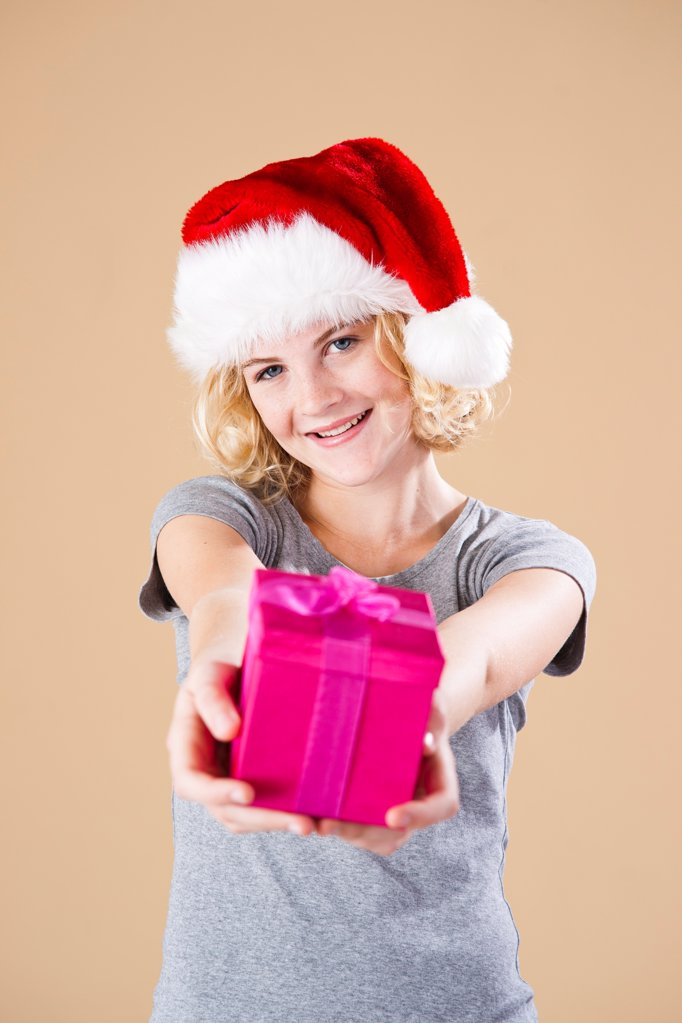 Teenage girl with santa's hat and present : Stock Photo