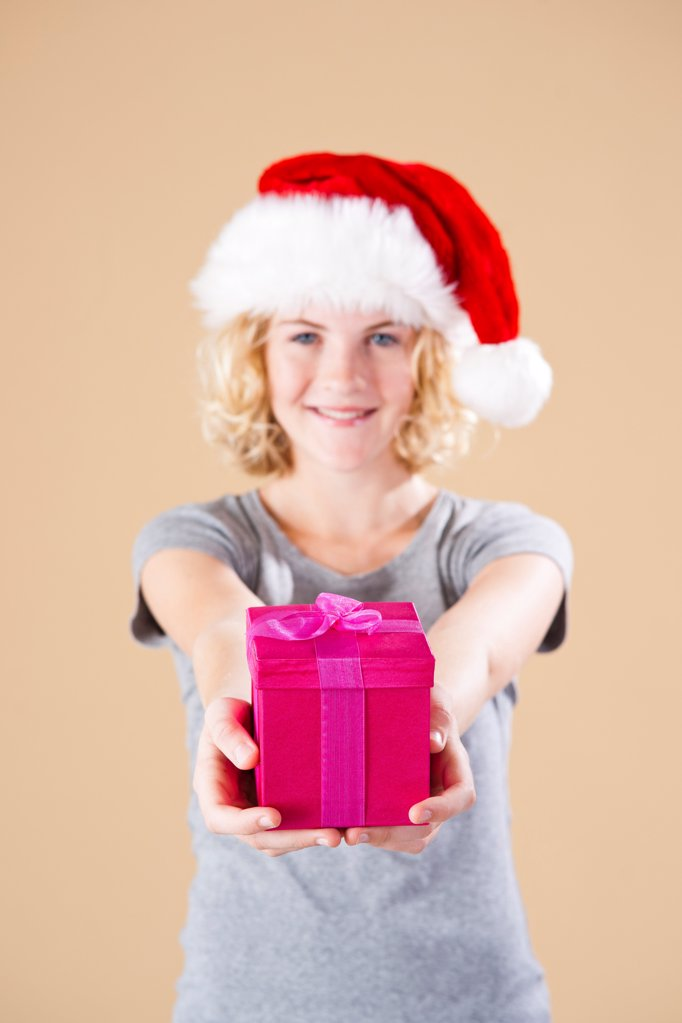 Stock Photo: 1841R-125000 Teenage girl with santa's hat and present