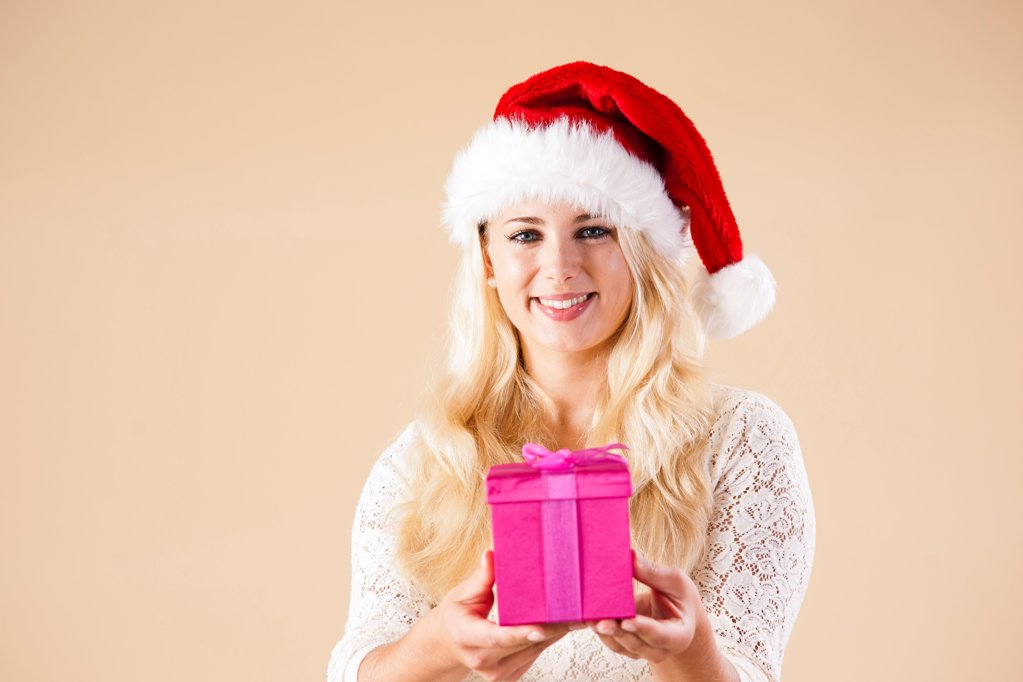 Young woman with santa's hat and present : Stock Photo