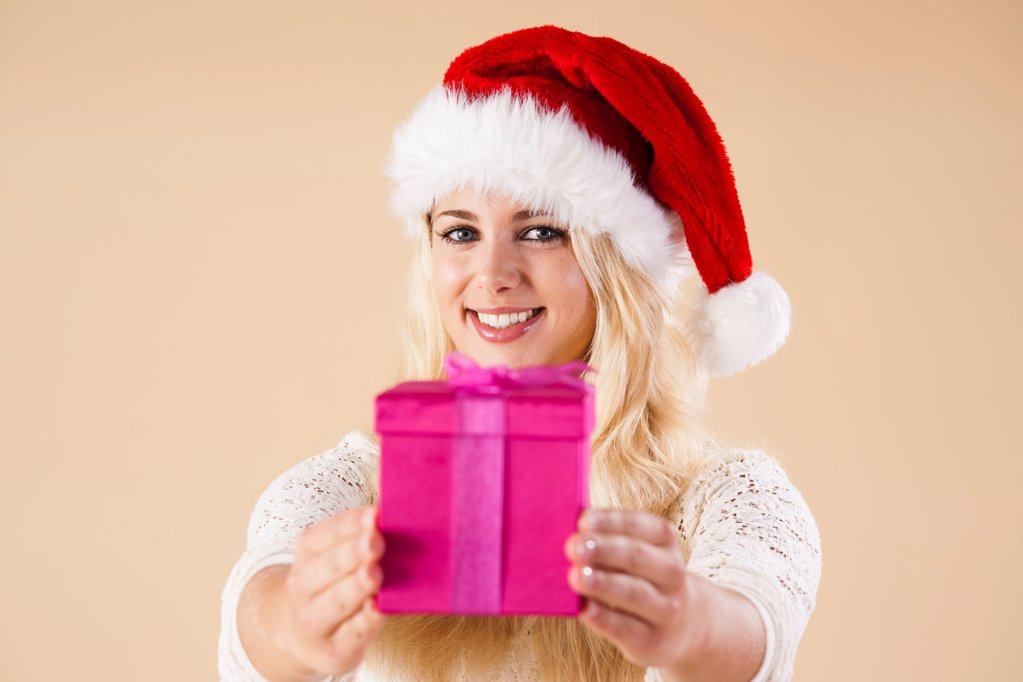 Stock Photo: 1841R-125004 Young woman with santa's hat and present