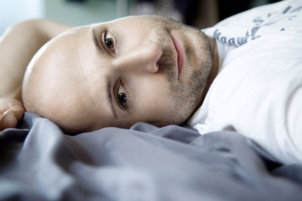 Stock Photo: 1841R-125070 Man with designer stubbles lying in bed, portrait