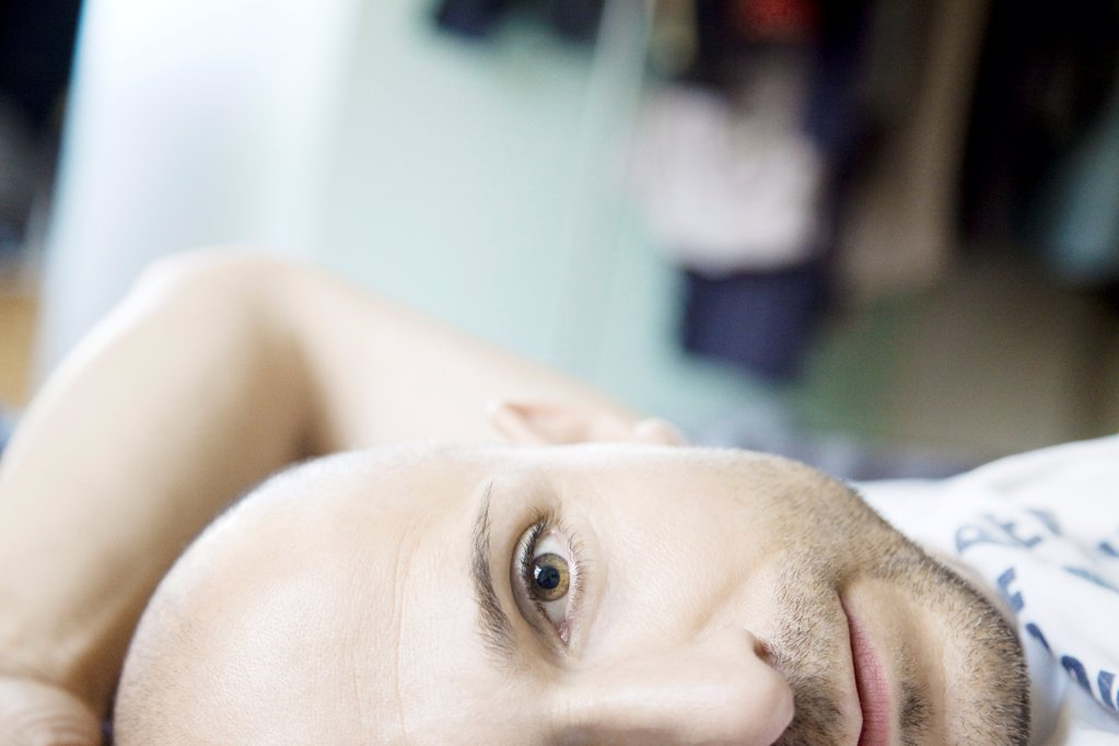 Man with designer stubbles lying in bed, portrait : Stock Photo