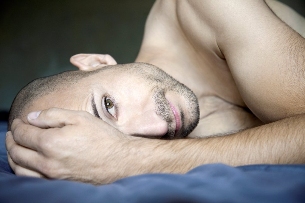Barechested man with designer lying in bed : Stock Photo